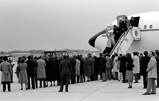The photograph shows former hostages walking down a flight of steps to exit an official plane; a crowd of people waits for them on the ground.