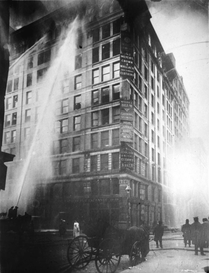 The photography shows firefighters attempting to put out the fire at the Triangle Shirtwaist Factory. The building is covered in ash.