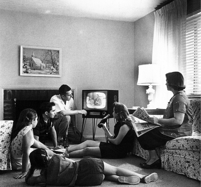 A family of six is gathered around a television set. The mother watches from the couch, while the father, the two sons, and the two daughters sit on the floor near the TV.