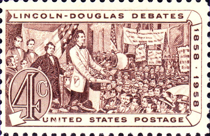 The postage stamp depicts Lincoln speaking to a large crowd of people. Douglas, standing with Lincoln on the stage, looks on in the background.