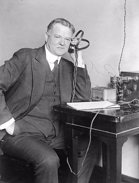 Photograph of Herbert Clark Hoover listening to a radio