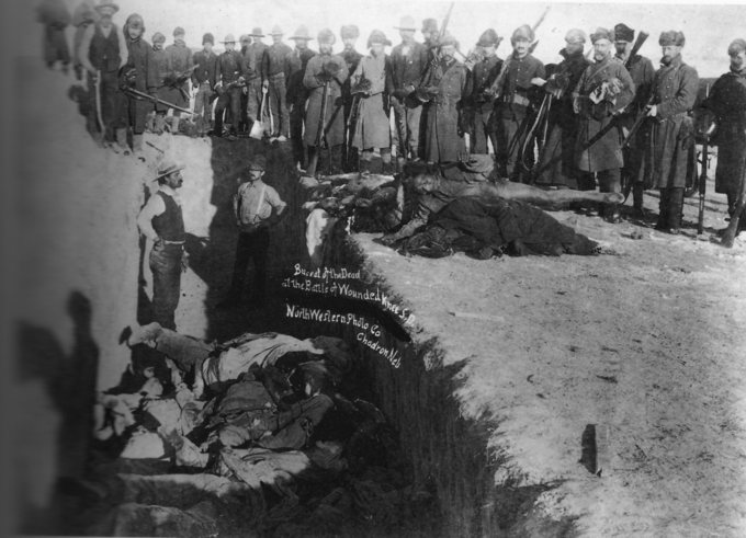 Burial of the dead after the massacre of Wounded Knee. U.S. Soldiers putting Native Americans in a common grave; some corpses are frozen in different positions