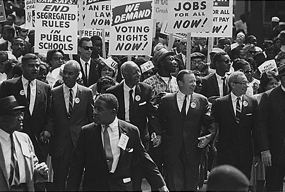 "The leaders in the front march hand-in-hand. Behind them, marchers carry signs that read ""End Segregated Rules in Public Schools,"" ""We Demand Voting Rights Now,"" and ""Jobs For All Now,"" among others."