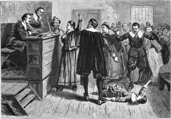 A young woman (presumably Mary Walcott) writhes on the floor as a judge and an unruly crowd look on.