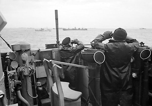 Photo of officers on the bridge of a destroyer, escorting a large convoy of ships keep a sharp look out for attacking enemy submarines.