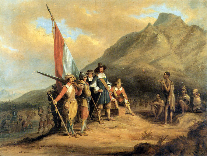 Painting of several Dutch explorers carrying the Dutch flag approaching native Africans. A large mountain looms in the background.