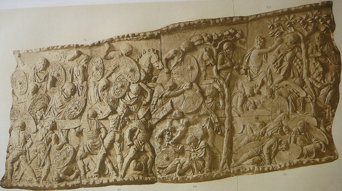 A stone relief of a battle scene between Romans and Dacians, depicting several men with shields battling and several men dead on the right hand side.