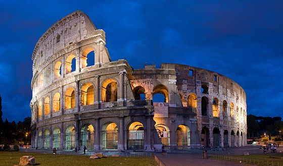 A photo of the Colosseum as it stands today, lit up at dusk.