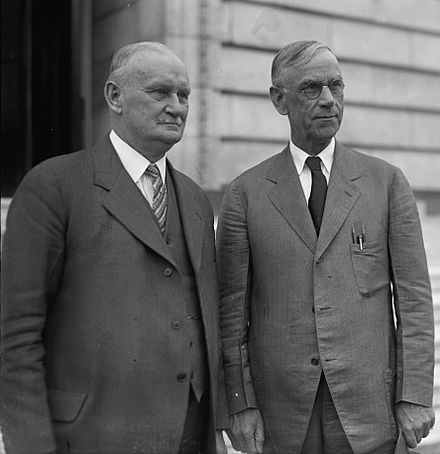 A photo of Willis C. Hawley (left) and Reed Smoot in April 1929, standing together outside a building. It is a close-up photo.