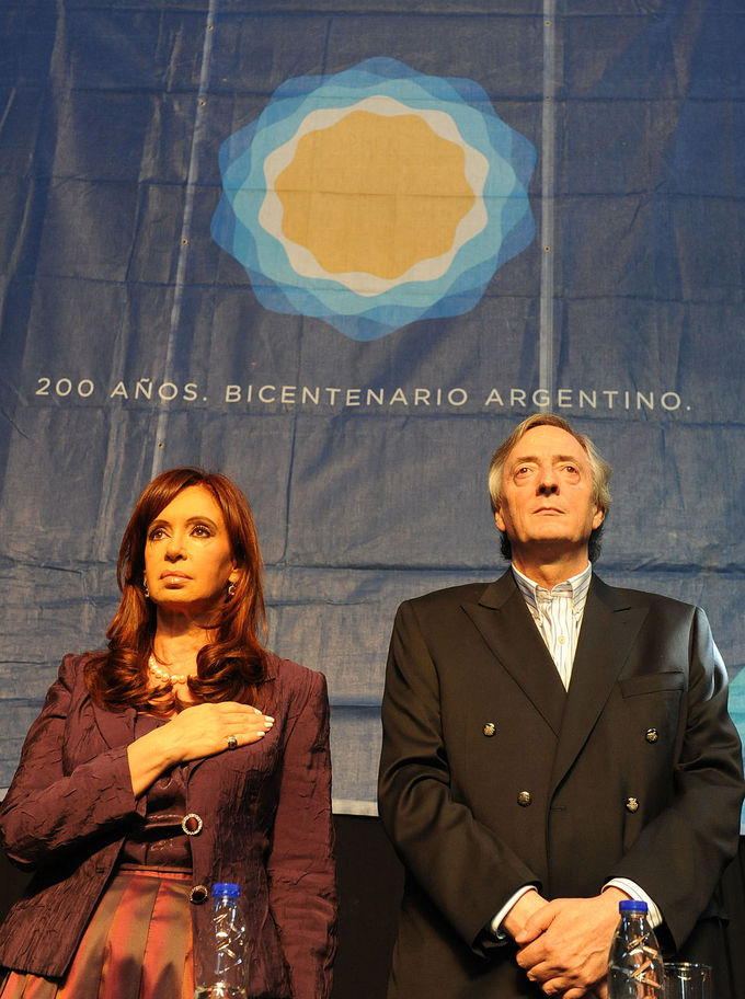 Photo of Cristina Fernández and Néstor Kirchner during the Bicentenario. She is standing on the left, holding her hand to her chest, he is standing next to her, hands folded in front of him.