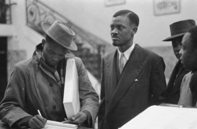 A photo of Patrice Lumumba, leader of the MNC-L and first Prime Minister, pictured in Brussels at the Round Table Conference of 1960, with several other Congolese men around him.