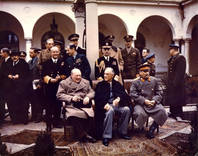 Photo of Churchill, Roosevelt, and Stalin at the Yalta Conference, surrounded by other government officials.