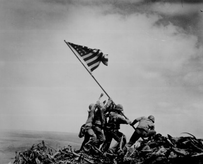 Iconic photo of several soldiers raising the American flag atop a hill on Iwo Jima.
