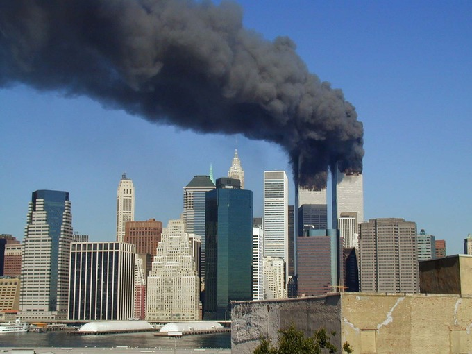 The former World Trade Center in Lower Manhattan during September 11 attacks in 2001. Both are on fire and smoking heavily.