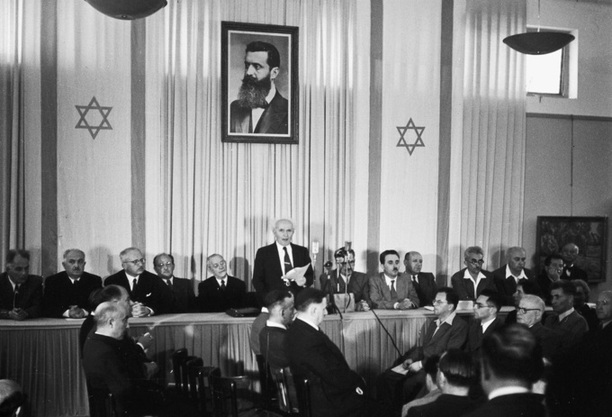 David Ben-Gurion proclaiming the Israeli Declaration of Independence on 14 May 1948. He stands at a conference table, surrounded by people. Above him hangs a picture of Theodor Herzl.