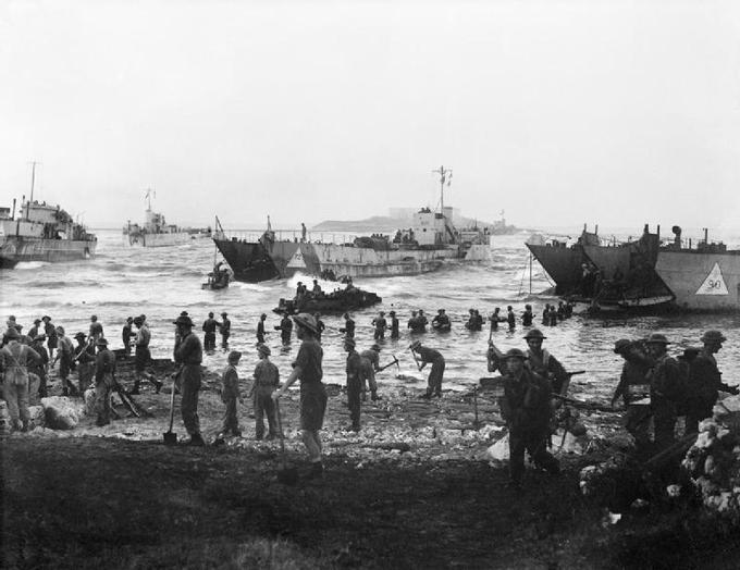 Image of British troops unloading stores onto the beach from tank landing craft on the opening day of the invasion of Sicily.