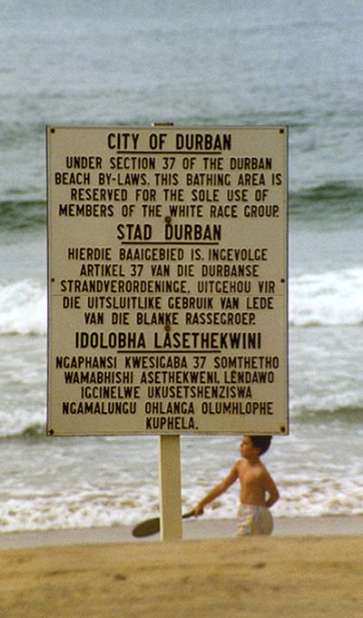 "Photo of a sign on a Durban beach that reserves it ""for the sole use of members of the white race group"", in English, Afrikaans, and Zulu."