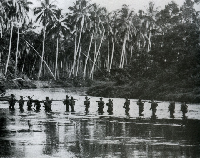Photo of American soldiers walking through water with palm trees and other plants in the background.