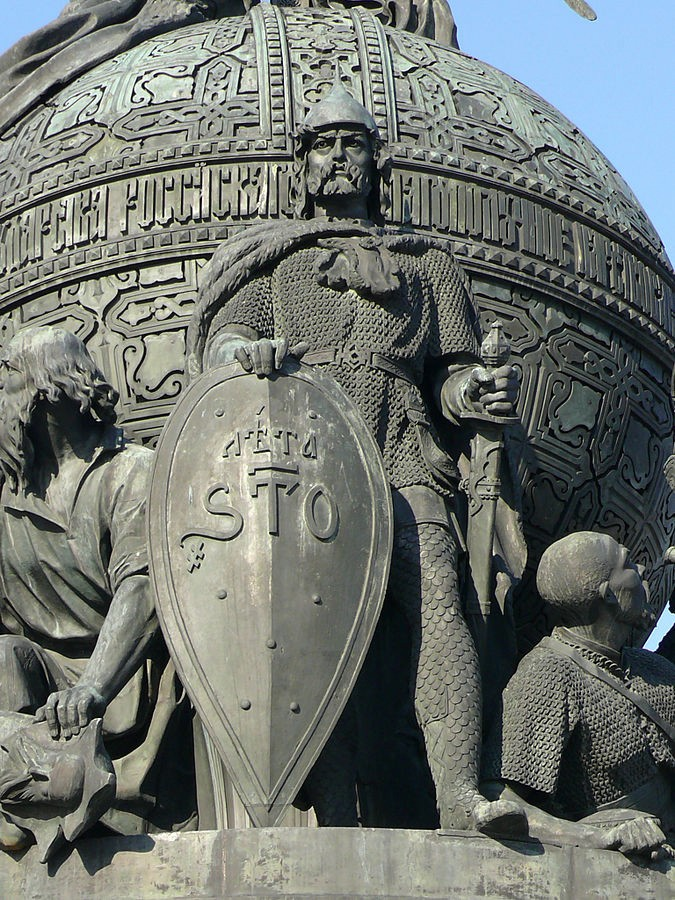 The monument depicts Rurik in full armor holding a shield in his right hand and a sword in his left hand.