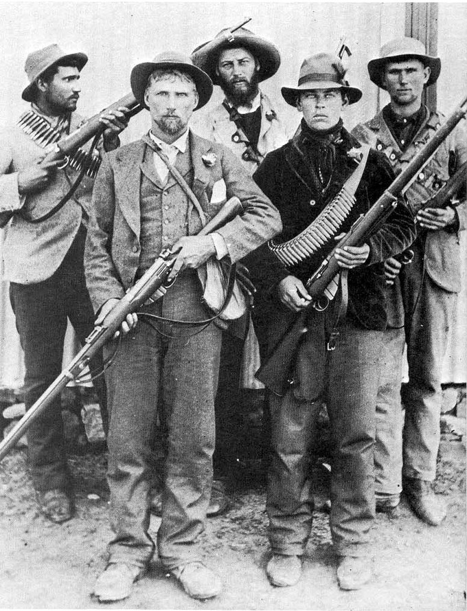 Photo of Boer soldiers, dressed in civilian clothes, armed with rifles and ammunition.