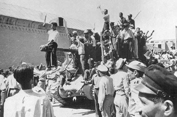 Photo of a tank covered by men celebrating the Coup in the streets of Tehran, 1953