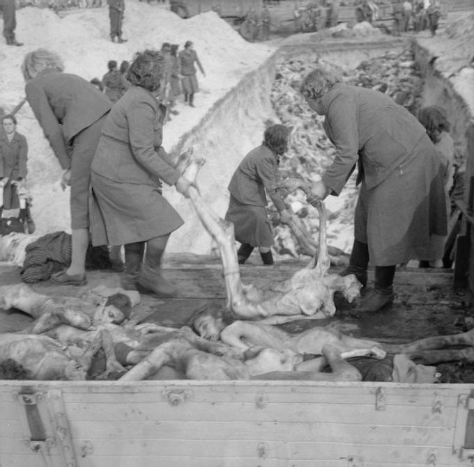 Photo of female German camp guards removing prisoners' bodies from lorries and carry them to a mass grave, inside the German Bergen-Belsen concentration camp, 1945