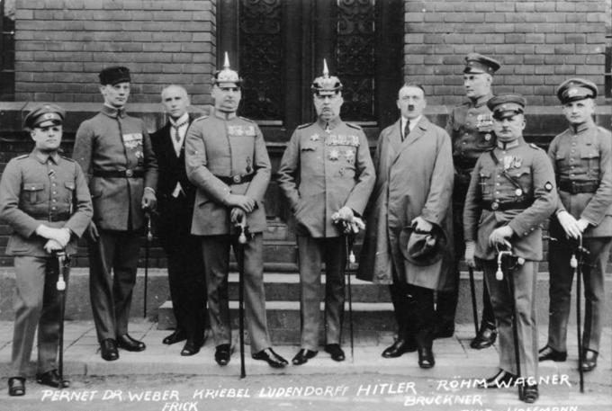 Photo of the defendants in the Beer Hall Putsch trial standing in front of a brick building.