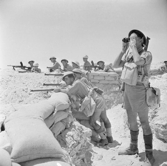 Image of armed British soldiers lined up against a wall of sandbags in the Alamein, Egypt.