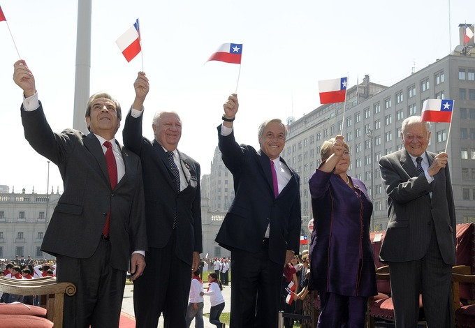 Photo of the five most recent presidents on Chile standing side by side, waving Chilean flags.