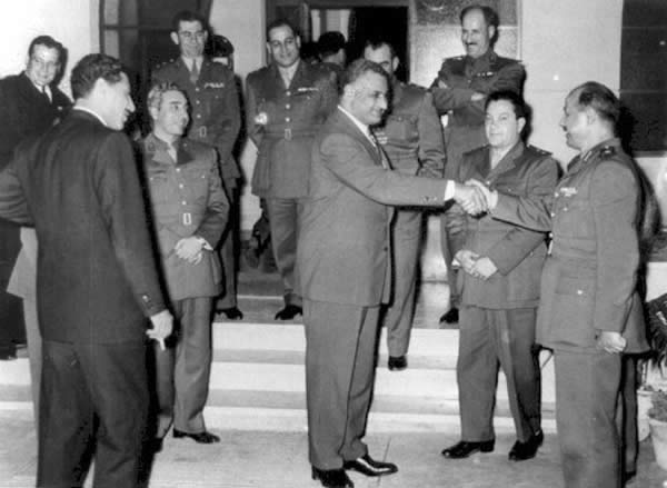 Photo of Nasser shaking hands with al-Bizri surrounded by a Syrian delegation.