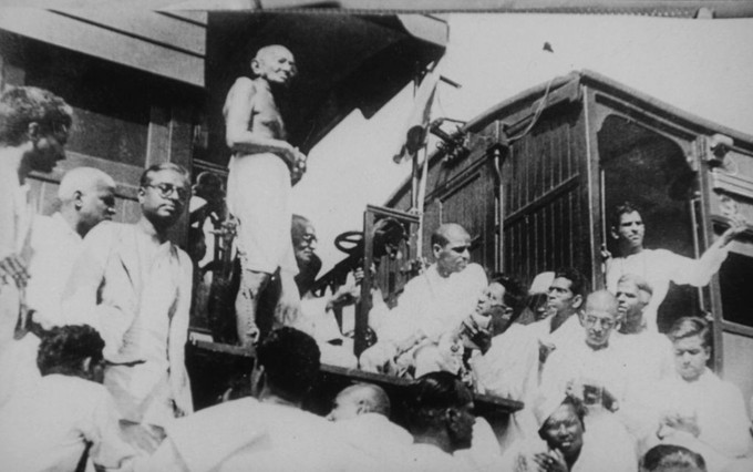 The photograph shows Gandhi speaking from a train. A crowd of men is gathered around and below him.