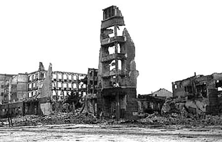 Photo of the ruined city of Stalingrad after WWII. Many buildings are collapsed entirely, while some have a few walls remaining.