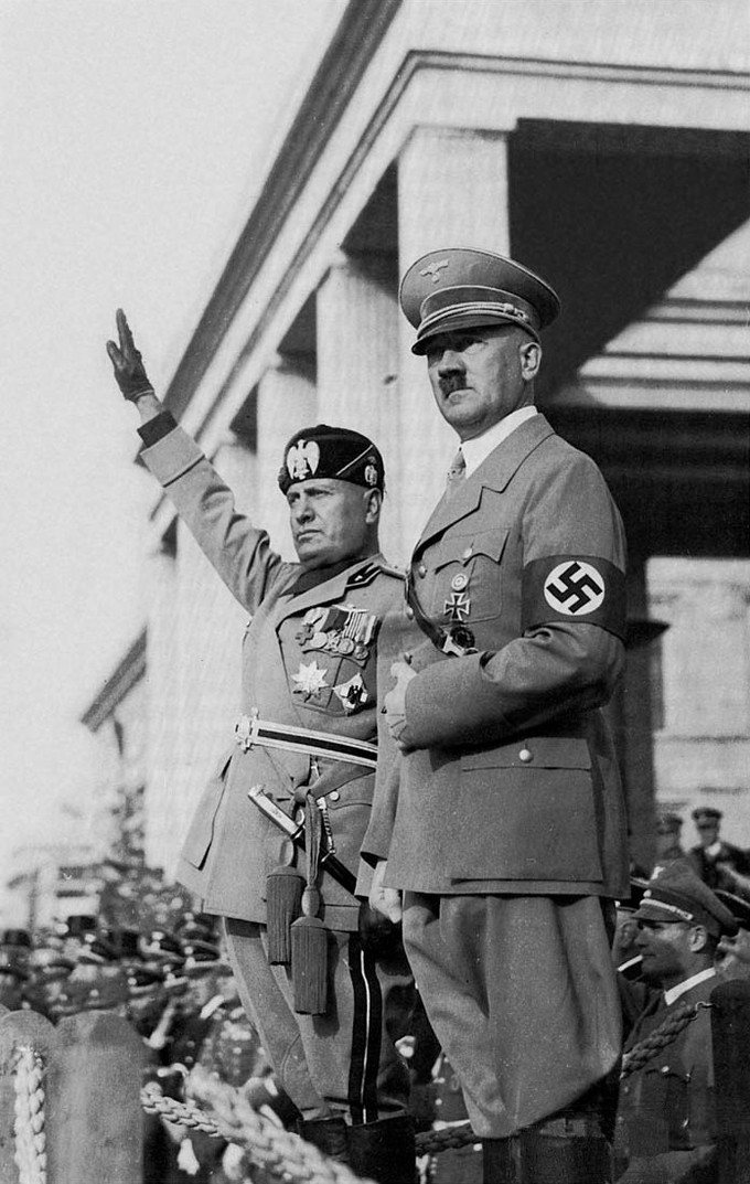 Photo of Mussolini and Hitler in uniform standing side by side.