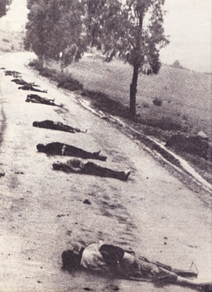Photo of several civilians laying dead across a road.