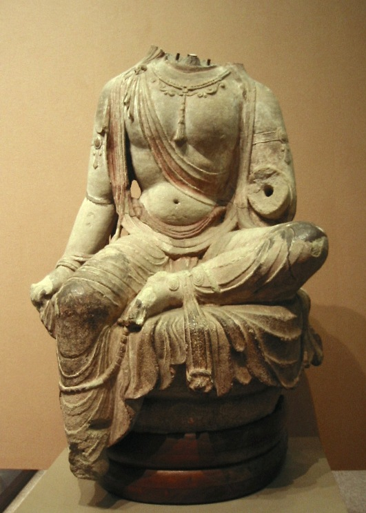 An image of a seated Buddhist saint, missing its head and left arm.