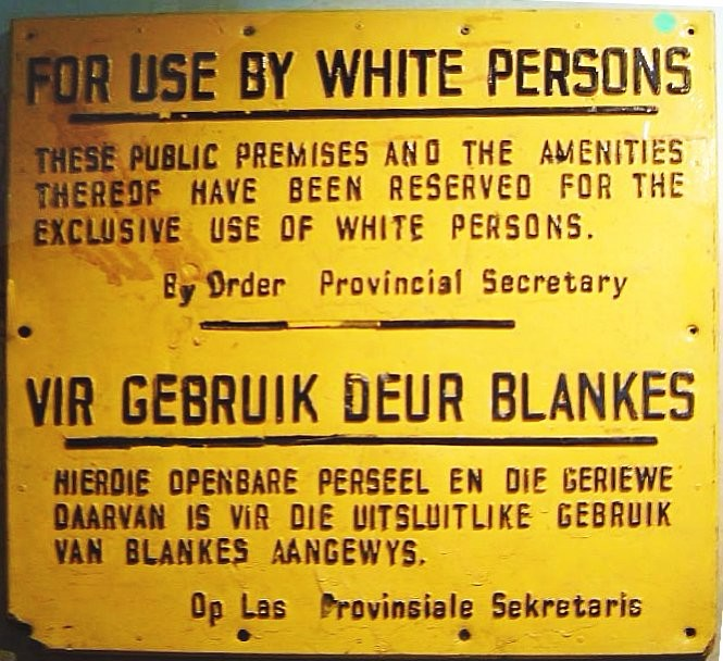 "The sign is written in English and Afrikaans. It reads: ""For use by white persons. These public premises and the amenities thereof have been reserved for the exclusive use of white persons. By order of Provincial Secretary."""