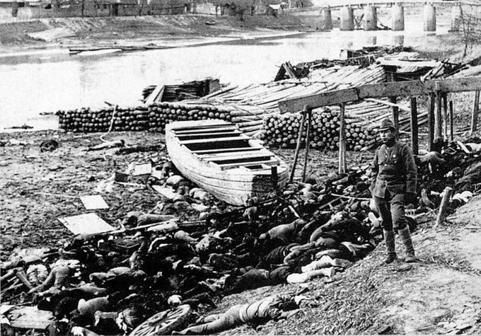 The corpses of massacred victims on the shore of the Qinhuai River with a Japanese soldier standing nearby.