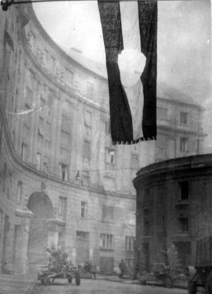 A photo of a Soviet Union flag with the communist coat of arms cut out hanging over a street. Military vehicles can be seen in the background.