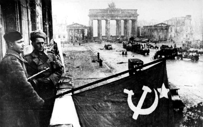 After the battle of Berlin, Soviet soldiers hoist the Soviet flag on the balcony of the Hotel Adlon in Berlin overlooking the street