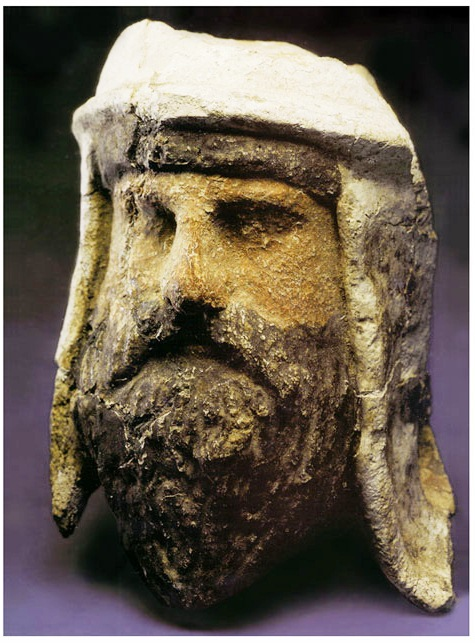 A sculpture of the head of a Zoroastrian priest wearing a white headdress.