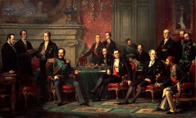 The painting depicts 15 men sitting and standing around a lavish parlor room.