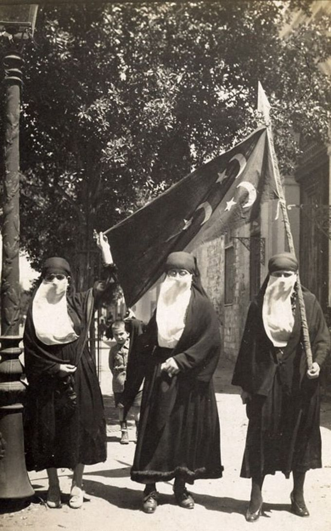 Image of Egyptian women wearing black dresses, black head covers, and white veils over their faces, carrying an Egyptian glad, demonstrating against British occupation during the revolution of 1919.