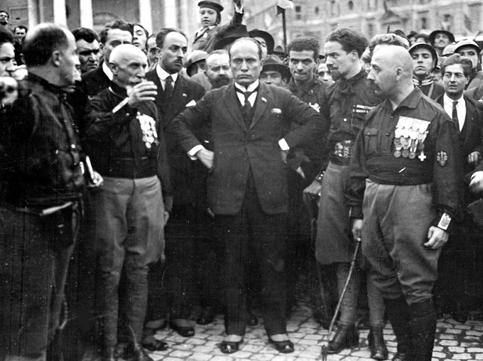 A photo of a crowd of mostly men, with Mussolini and other fascist leaders in the center.