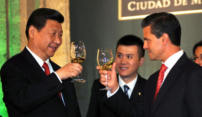 Photo of President Enrique Peña Nieto with President of China Xi Jinping, standing, looking at each other with smiles, toasting with a glass of white wine.