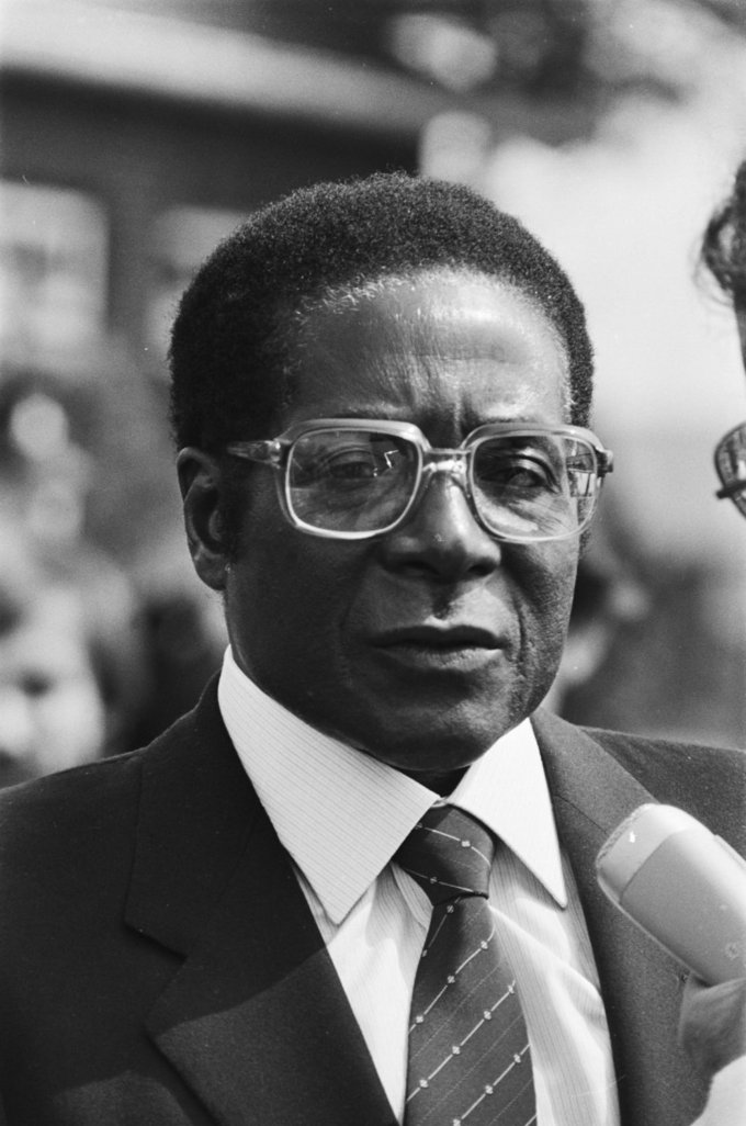 Photo of Robert Mugabe in 1982 with a suit and tie and think rimmed glasses.