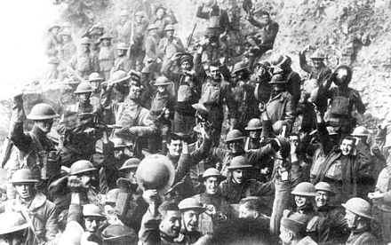 A large group of men in military outfits are smiling and raising up their helmets.