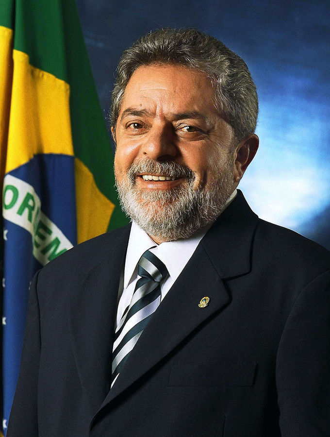 Close-up photo of President Luíz Inácio Lula da Silva in front of a Brazilian flag.