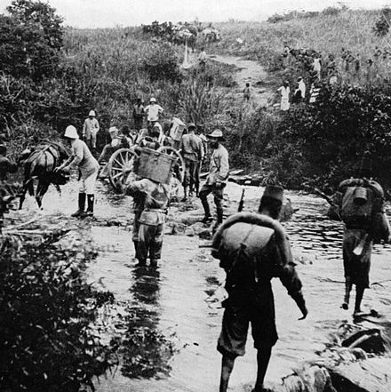 A photo of Force Publique soldiers in the Belgian Congo in 1918, walking through a river with supplies.