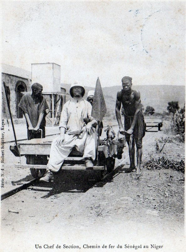 "A photo of a white French ""Section Chief"" being pushed on a rail cart by two black African workers in Mali, 1904."