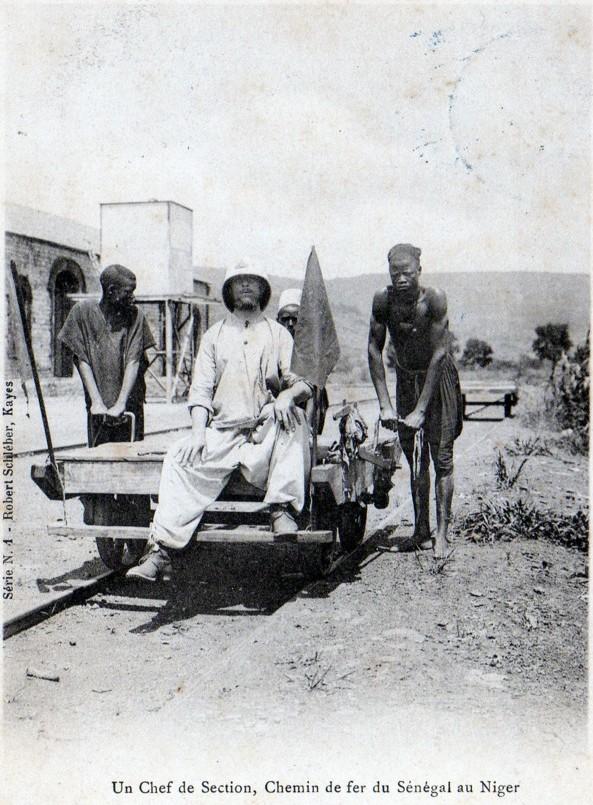 """Uma foto de um """"chefe de seção"""" francês branco sendo empurrado em um carrinho de trem por dois trabalhadores negros africanos em Mali, 1904."""